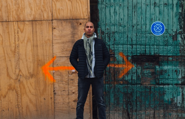 student against wall with detour arrows painted on it behind him