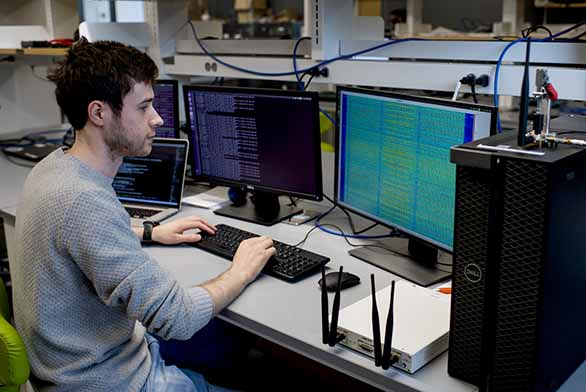 man at computer area with double monitors showing columns of coding