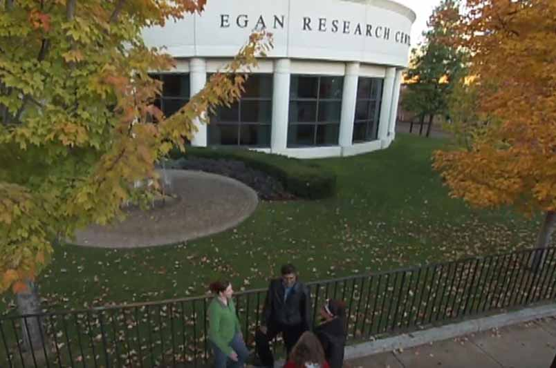 three people outside of egan research center building