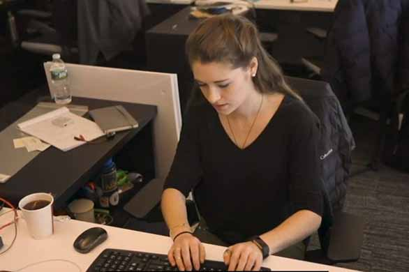 student working on keyboard at desk in office
