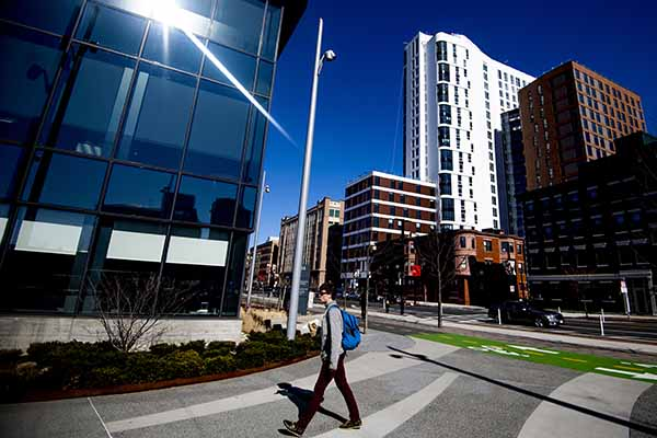 student walks across busy Boston street with city buildings lining the street