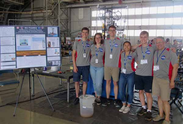 five students and a faculty member pose in front of a research poster in a warehouse