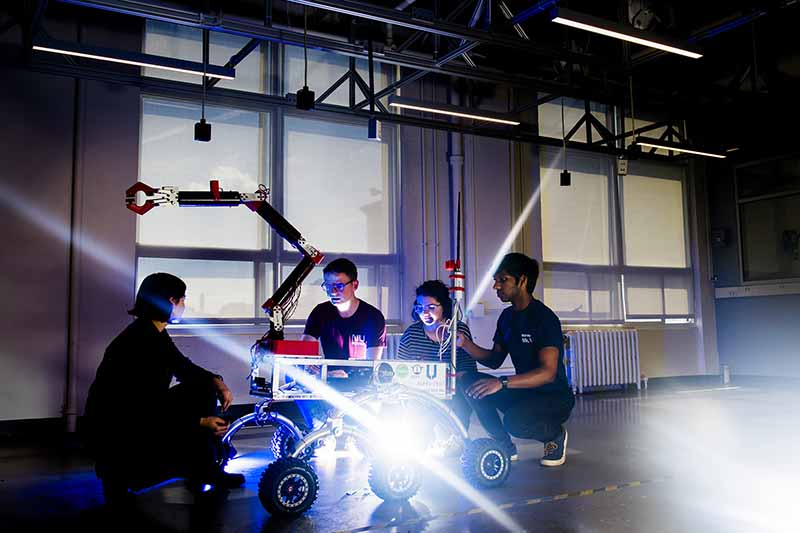 four students work on rover robot in warehouse