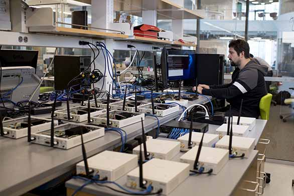student in lab with multiple wireless receivers working on a computer in lab
